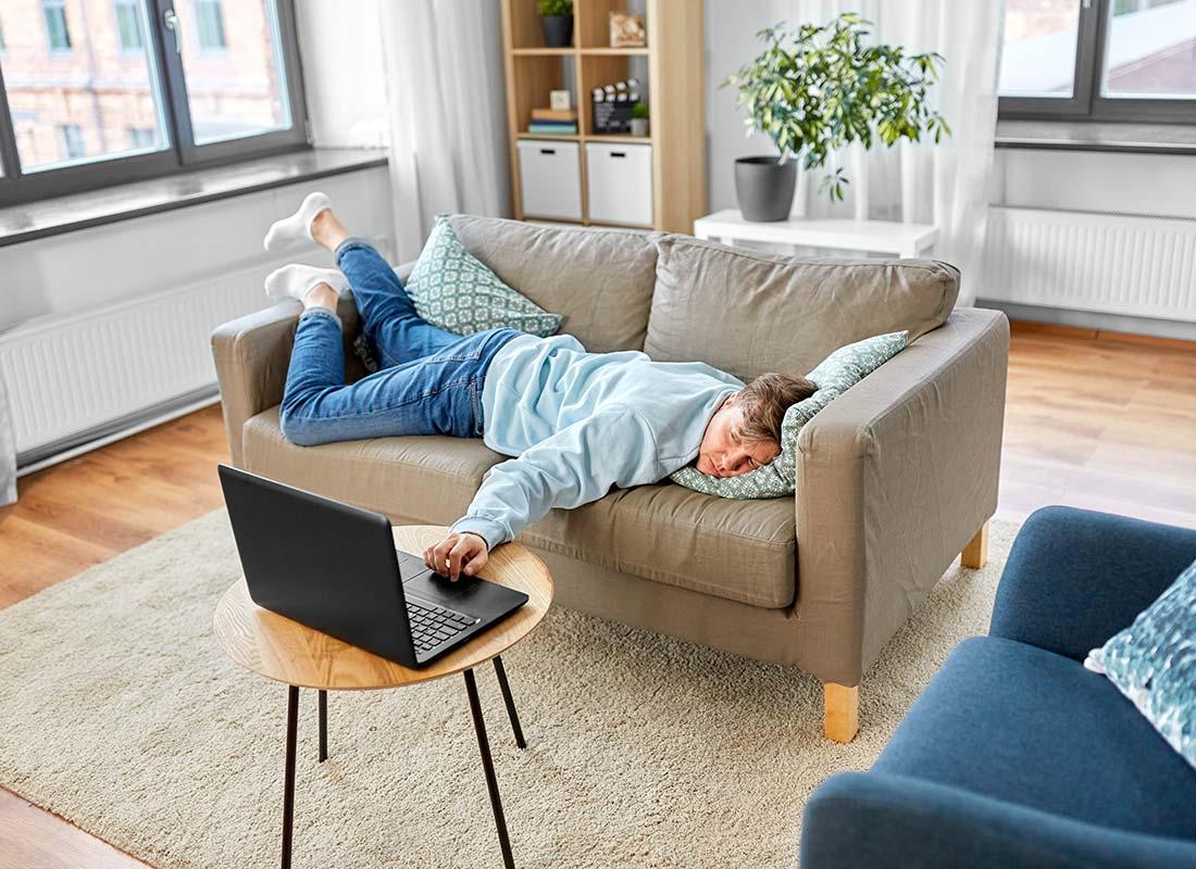 Un homme en train de calculer sur son ordinateur le temps qu'il gagne à ne pas faire le ménage