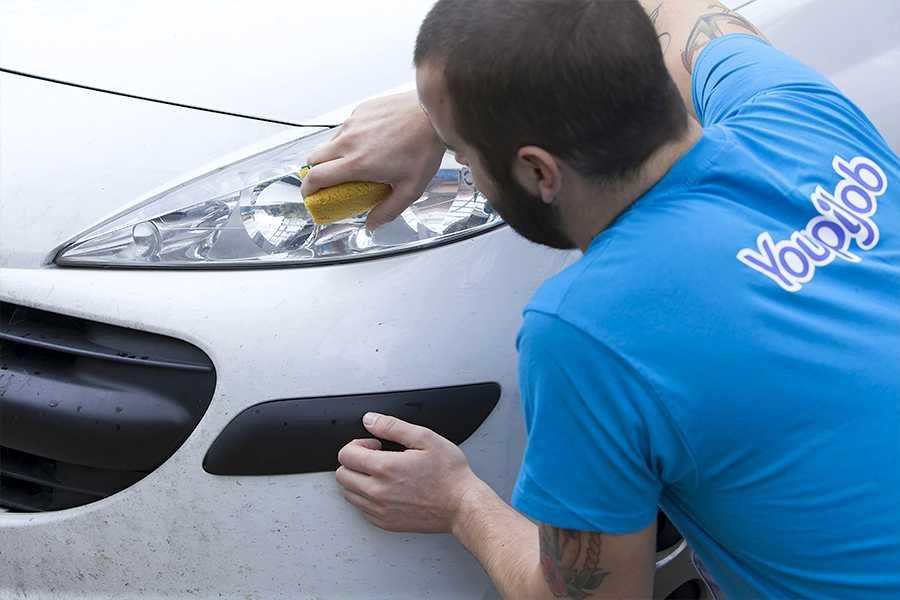 Aide ménagère qui effectue un lavage automobile à domicile
