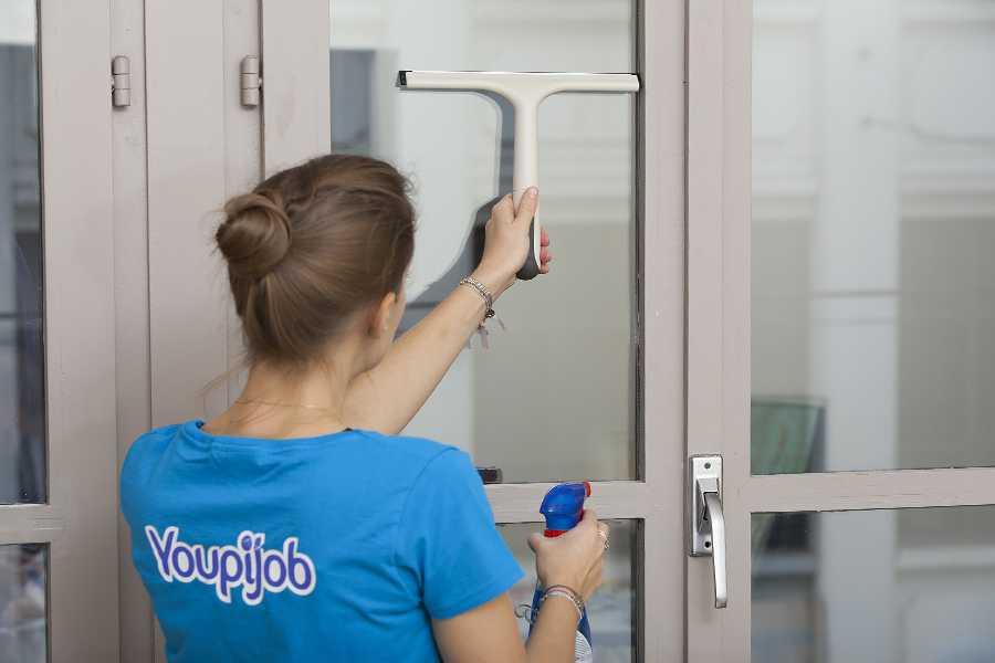 Aide ménagère qui effectue un nettoyage de vitres à domicile