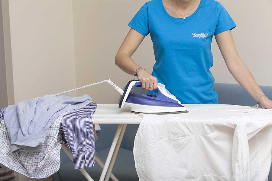 Femme de ménage qui effectue un repassage à domicile