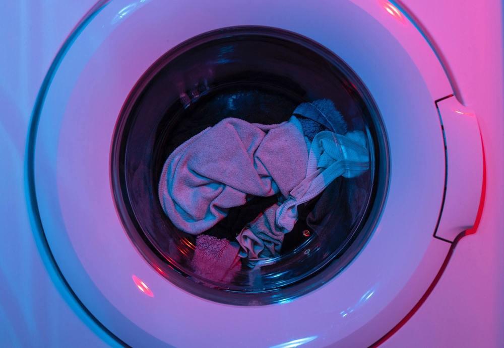 une machine à laver avec du linge blanc