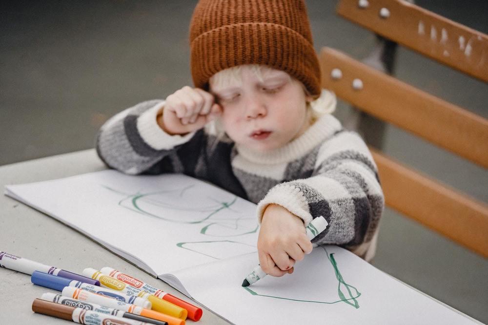 Un enfant utilise des feutres de couleur