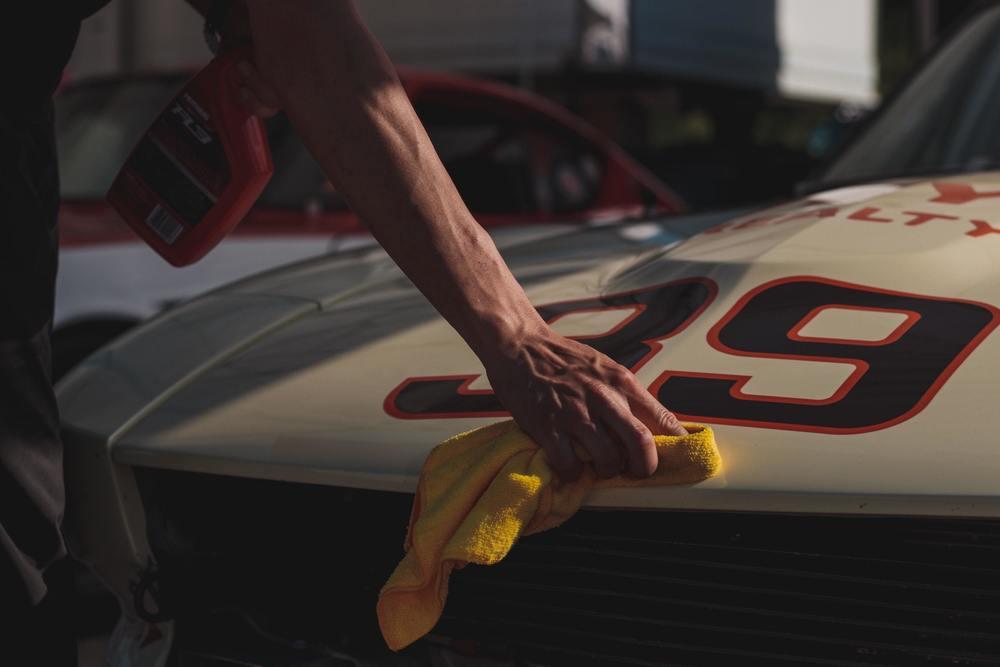 Un homme fait briller sa voiture avec de la cire
