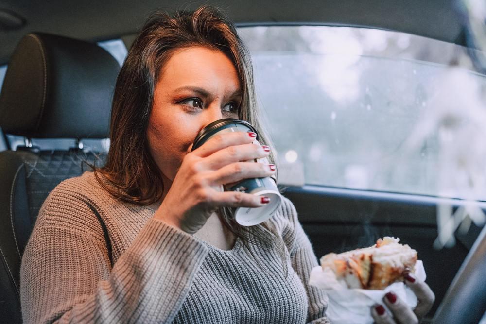 Une femme en train de manger dans sa voiture