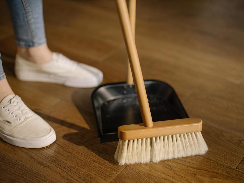 une femme de ménage fait la poussière