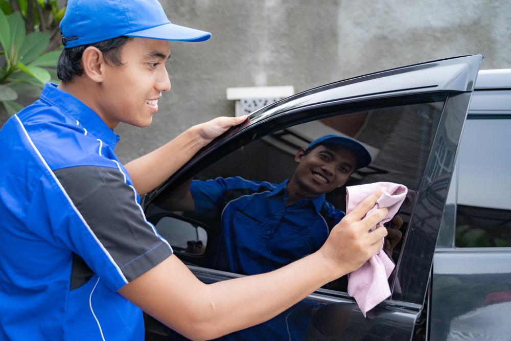 Un prestataire en train de laver la voiture de son client à domicile