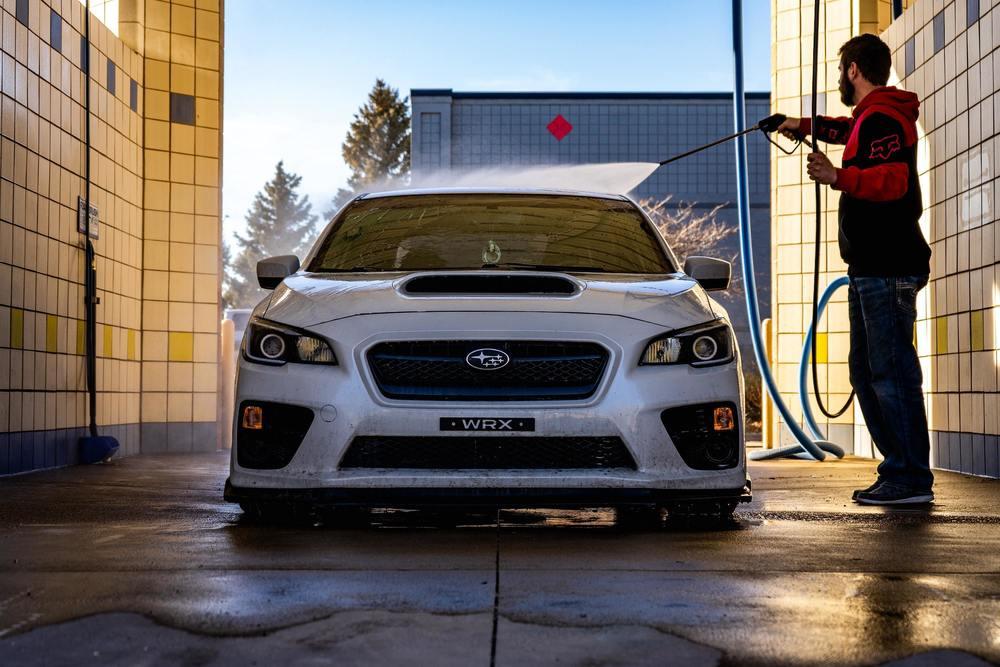 Un homme nettoie sa voiture au Karcher