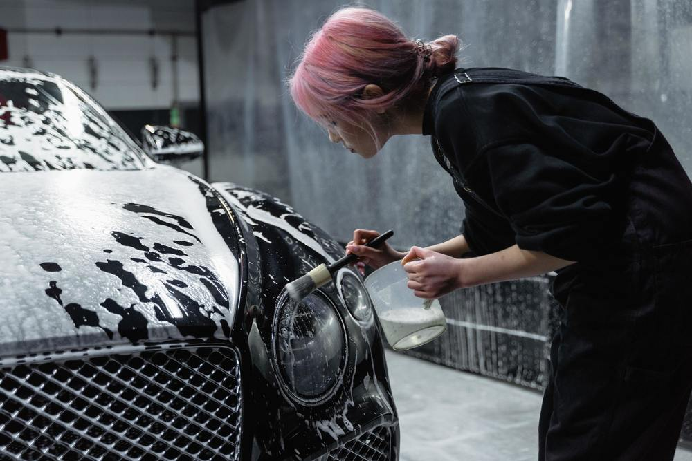 Une femme en train de laver un phare de voiture