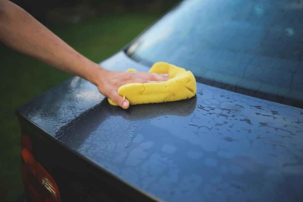 Un homme polish sa voiture